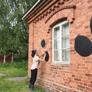 (PHOTO: Valentina Carini) Valentina is decorationg the brick walls of her art studio at the art centre in the Finnish countryside.