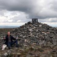 (FOTO: Mikael Diehl) Auf dem Gipfel des Pallastunturi: Mika vor dem Denkmal von Paavo Nurmi. Im Hintergrund ziehen bereits dunkle Wolken auf.