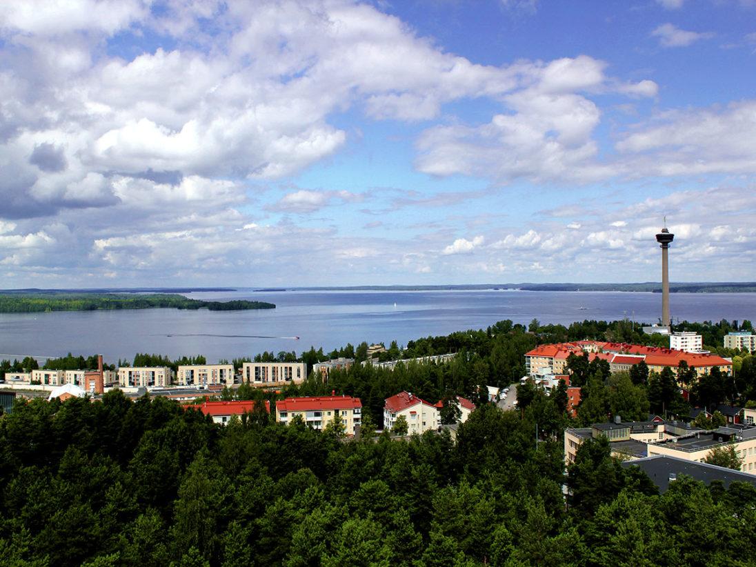 Blick auf die Stadt Tampere, im Hintergrund sieht man grüne Wälder und blaue Seen, rechts ragt der Aussichtsturm über die StadtNäsinneula